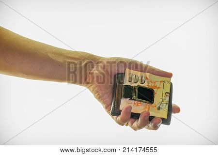 Close up of a man's hand holding a money clip / wallet.