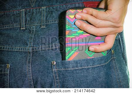 A man taking out his wallet from his jean's back pocket.