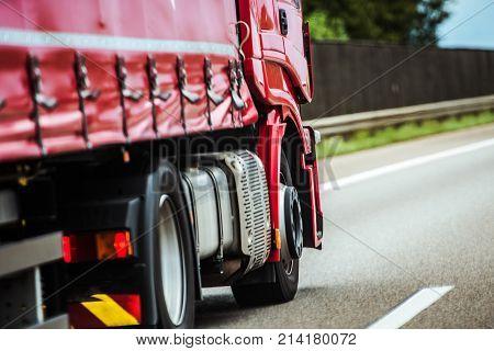 Red Speeding Semi Truck on the European Highway. Transportation Industry.