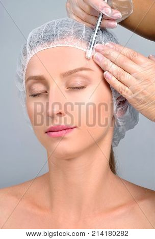 Woman Is Getting Injection Over Eyebrow. Anti-aging Treatment And Face Lift. Cosmetic Treatment And