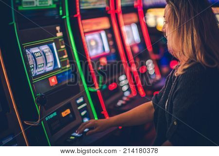 Slot Machine Casino Playing. Caucasian Woman in Her 30s Playing Modern One Handed Bandit Slot.
