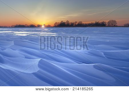 winter dawn on the frozen lake whimsical snow patterns in the rays of dawn