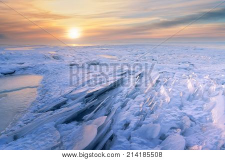 winter dawn on the frozen lake / whimsical snow patterns in the rays of dawn