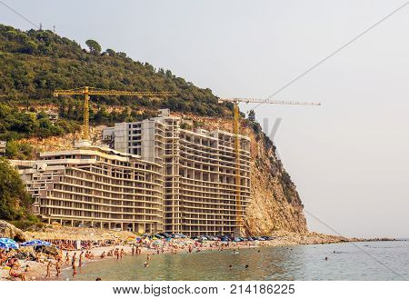 a construction crane and a building inscribed uphill. Construction of a five-star hotel on the beach in Montenegro 2017year.