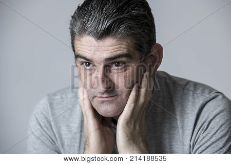 portrait of 40s to 50s sad and worried man looking frustrated and thoughtful in worried and pensive face expression isolated on grey background in sadness frustration and life problems concept