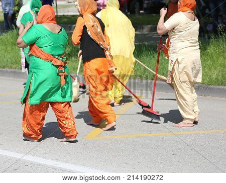 Sikh Religious Event And Barefoot Women Who Sweep The Street In