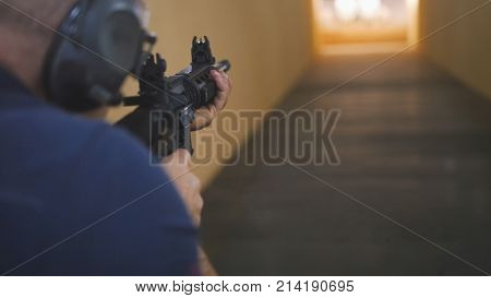 Man instructor have shooting with a Machinegun at the shooting gallery, close up