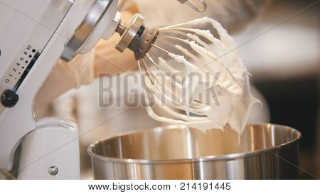 Process of cooking meringue whipped egg whites on mixer whisk , close up