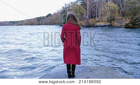Young girl with her hair stands near the water in the cold season. Back view. Young woman standing near a lake.