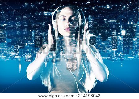 Portrait of attractive young woman listening to music through headphones on abstract upside down night city background. Hobby leisure relaxation concept. Double exposure