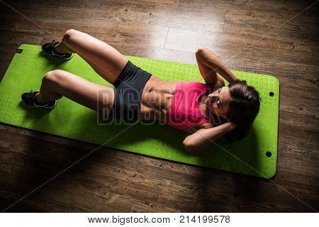 Sports girl does crunches while lying on a press on the green Mat in the fitness room.