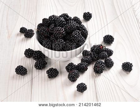 Fresh black berries in bowl on wooden table. Close up high resolution product. Harvest Concept