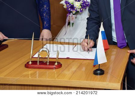 Unknown Russian bride and groom stand at the registration office next to the registrar in Russia.