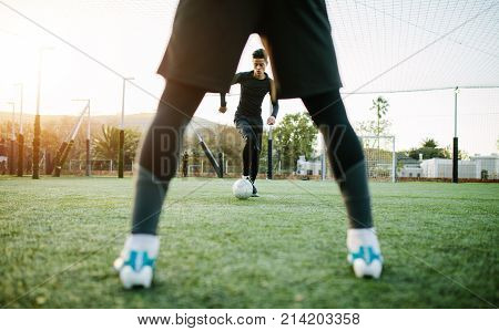 Soccer players during team practice in field. Young footballer playing on the sports grass field.