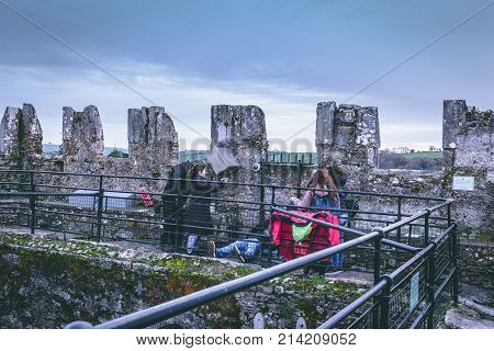 November 17th, 2017, Blarney, Ireland - Tourists kissing the famous Blarney stone at Blarney Castle, a medieval stronghold in Blarney, near Cork, Ireland, and the River Martin.