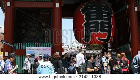 Tokyo, Japan - April 19, 2017: crowded people in front to red giant lantern of Kaminarimon Gate in Senso-ji, the oldest temple in Tokyo, Asakusa. The Japanese word on the lantern means THUNDER GATE.