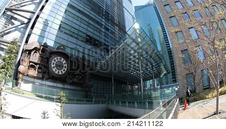 Tokyo, Japan - April 20, 2017: Nippon Television HQ with Japanese white-collar business workers walking in Shiodome area. Ghibli clock at Nittele Tower in Shinbashi. fisheye effect.