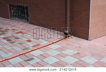 Roof gutter downspout pipe with drain in pavement. Rain gutter pipeline drainage.