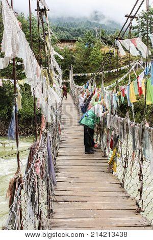 Paro, Bhutan - September 14, 2016: Tourists On The Iron Bridge Of Tamchog Lhakhang Monastery, Paro R
