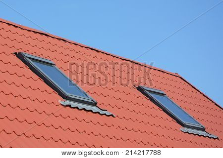 Skylight Attic Windows with Red Metal House Roof. Close up on Attic skylight windows waterproofing.