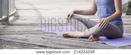 Young woman practicing yoga during luxury yoga retreat in Asia, Bali, meditation, relaxation, getting fit, in abandoned temple background, praying hands