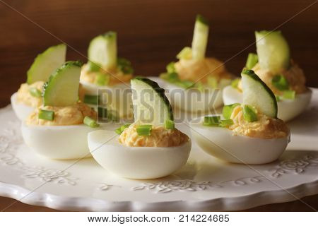 Spicy deviled eggs garnished with cucumber and leek on white plate. Wooden rustic background .