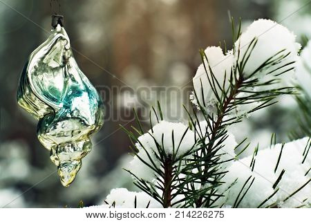 old handmade glass Christmas ornament - fascinatingly shiny sea shell - on a living fir against the background of a blurry real winter forest