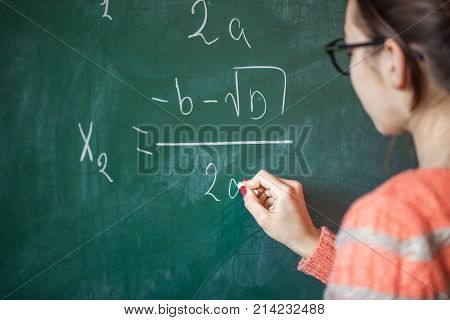 Girl With Chalk In Her Hand Solves A Mathematical Problem On The Blackboard
