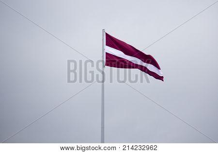 latvian flag on dark grey sky in latvia