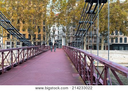 Lyon France--November 5 2017--Two cyclists are riding thier bicycles over the Saint Vincent Bridge in Lyon. Editorial Use Only.