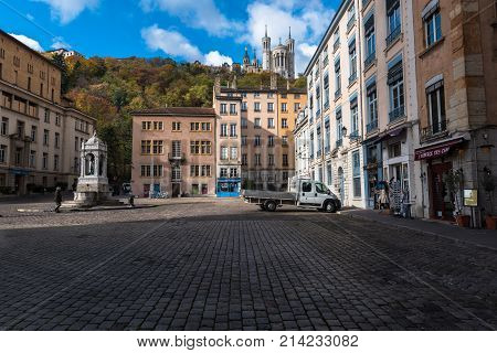 Lyon France--November 6 2017--Shops and Restaurants in the Old City section of Lyon. The Bassilica of Notre-Dame de Fourviere is on a hill in the background. Editorial Use Only.