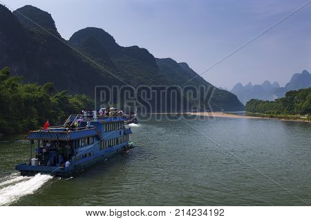 Yangshuo China - August 1 2010: Passenger boats with tourists in the Li River with the tall limestone peaks in the background near Yangshuo in China Asia.