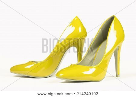 Lacquered shiny yellow shoes high heels on white background.