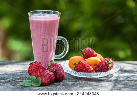 glass with strawberry apricot smoothies on a wooden table a background of a green garden. A basket with strawberries and apricots bananas near