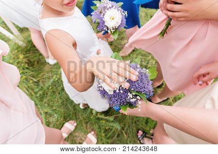 Little sweet girlfriend of the bride brags her ringlet to her adult friends with her hand on the bouquet on the exit registration