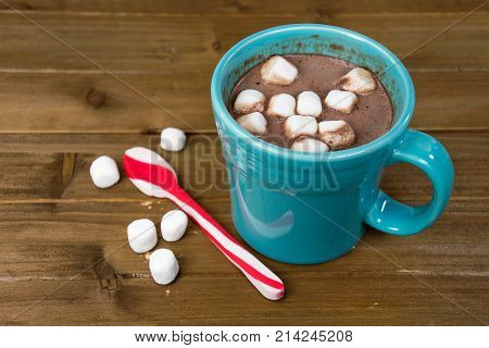 hot chocolate drink in turquoise mug with marshmallows and Christmas peppermint spoon on rustic wood