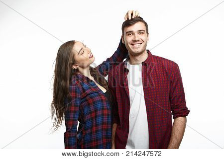 Charming positive young woman with long dark hair smiling admiring her boyfriend and stroking his head as an expression of approval or congratulation feeling proud of him praising for good job