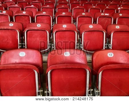 Empty red plastic seats in a football stadium.