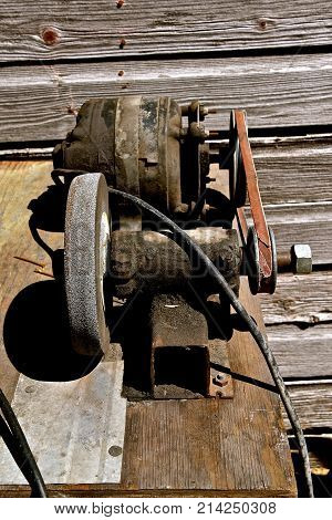 Old home made grinding wheel operated by a pulley and electric motor.
