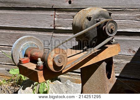 Old homemade grinding wheel operated by a pulley and electric motor