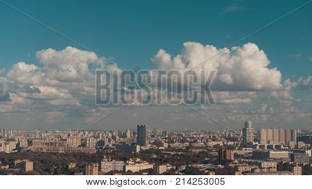 View from high elevation of metropolis summer cityscape with multiple residential and office buildings high-rises public parks and stadium under construction; beautiful cloudscape; Moscow Russia
