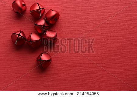 Bright red jingle bells against red background with copy space.