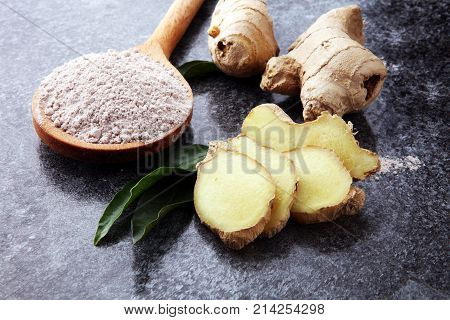 Fresh ginger root and ground ginger spice on dark background.