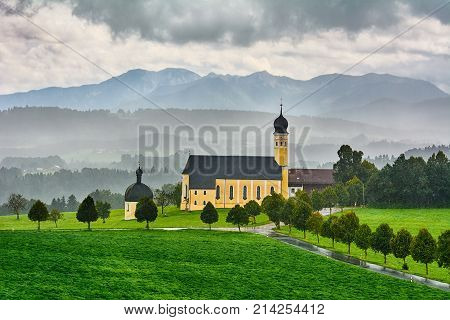 Yellow Church in Front of Alps Austria