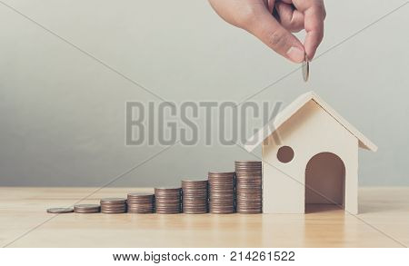 Property investment and house mortgage financial concept Hand putting money coin stack with wooden house