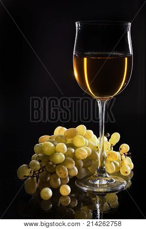Glass of wine and a bunch of grape on a studio glass background