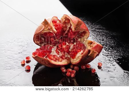 Pomegranate on a glass background with drops of water