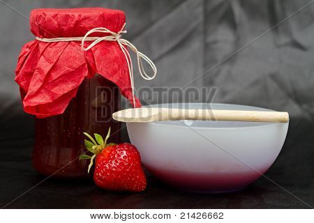 Glass pot with strawberry jam against black background poster