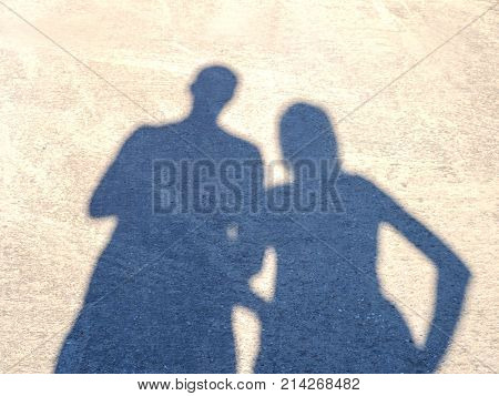 A shadow of a couple on the asphalt in a bright sunny summer day. Heart in the center of the frame formed by shadows. Strong love.