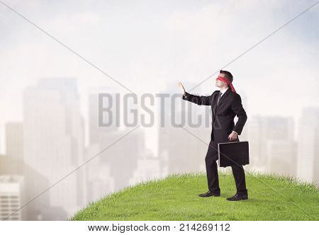 Young blindfolded businessman steps on a a patch of grass with a city in the background